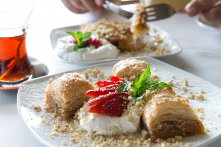 Baklava pairs well with hot turkish tea and served with Strawberry and full fat cream and garnished with mint leaves Imagens