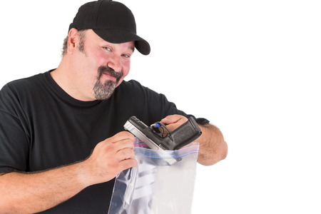 criminologist: Crime scene investigator founds a gun, he has a sure look on his face while he is placing gun in to a evidence bag Stock Photo