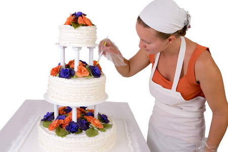 gum paste: Baker lady with a white bandanna giving to a wedding cake final touchups, cake has fondant ruffles on the side and decorated with orange and purple gum paste roses