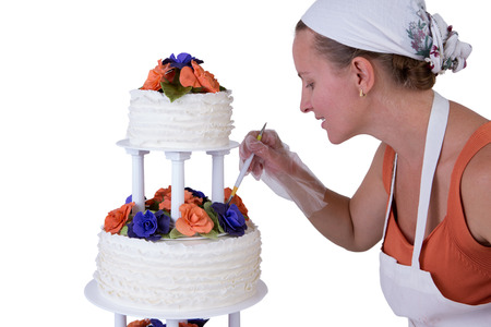 gum paste: Baker lady giving to a wedding cake latest small retouches, cake has fondant ruffles on the side and decorated with orange and purple gum paste roses