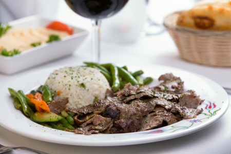 gyros: Gyro Doner garnished with rice Pilaf and vegetables partnered with hummus, pita bread and red wine Stock Photo