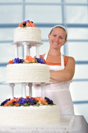 Happy baker lady happily smiling large infront of her cake with her apron and white bandanna, cake has fondant ruffles on the side and decorated with orange and purple gum paste roses photo