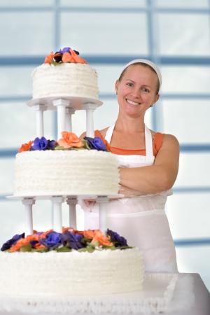 decoracion de pasteles: Panadero feliz mujer sonriendo feliz grande delante de su pastel con el delantal y pañuelo blanco, pastel de fondant tiene volantes en el lado y decorado con rosas de pasta de goma de color naranja y morado