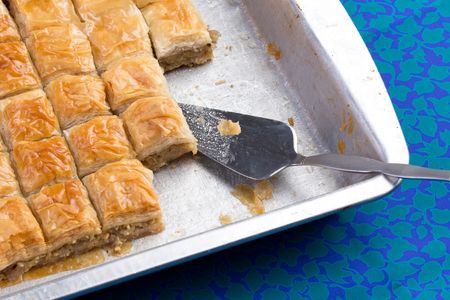 serv: Home made baklava ready to serv from aluminum tray with brushed stailes-steel spatula