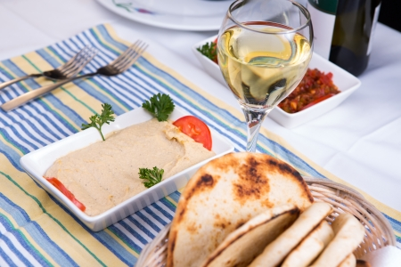 Hummus paired with white wine and pia breads and served on a blue striped cotton placement Stock Photo - 22438570