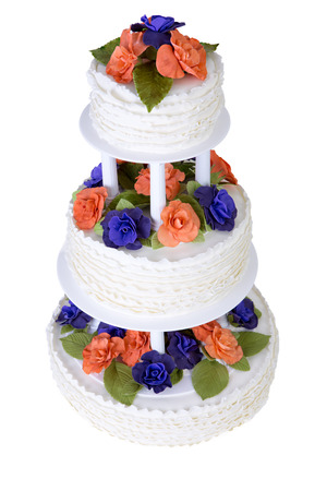 Isolated three tier ruffled white wedding cake decorated with orange and purple roses and green leafs photo