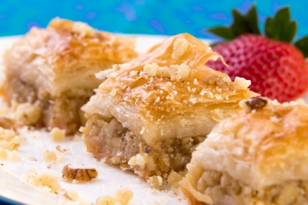 fillo: Three pieces of golden color baklava garnished with walnuts and strawberry, macro shot Stock Photo