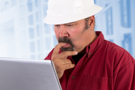 Hardhat worker perplexed, working on the tough issues with his laptop, he has a serious thoughtful look that he values his job, he is wearing red shirt and isolated on bluish background, copy space on hardhat and laptop photo