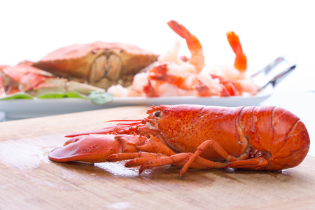 Prepearing dungenesscrab, red lobster and shrimps in the kitchen on the cutting board, copy space at the top Foto de archivo