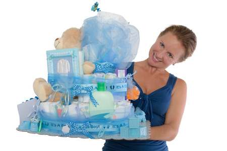 Pretty lady presenting a baby diaper cake with different items for the expectant family and their boy, Isolated on a white background, photo
