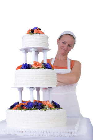 Baker lady giving to a wedding cake latest proud look in her apron and white bandanna, cake has fondant ruffles on the side and decorated with orange and purple gum paste roses photo