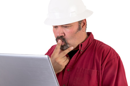 Hardhat worker working or surfing with his laptop, he has a puzzled look, he is wearing red shirt and isolated on white background, copy space on hardhat and laptop photo