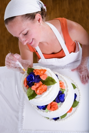 Woman with white bandanna giving to a wedding cake latest small retouches with love, shot from above photo