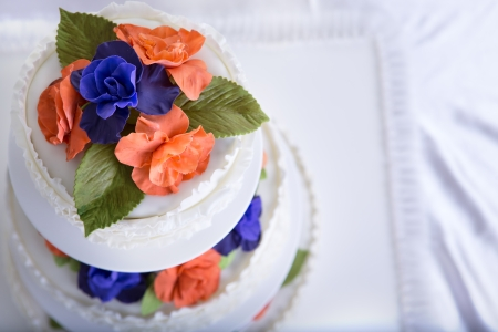 gum paste: Three tier fondant  ruffled white wedding cake decorated with orange and purple gum paste roses and green leafs, shot from above Stock Photo