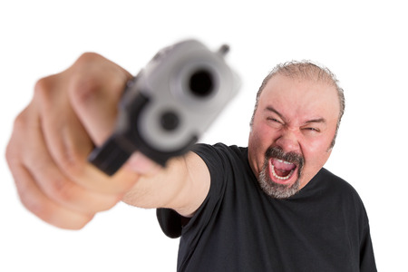 Middle age man screams out loud wile holding his gun at his left hand pointed at you photo
