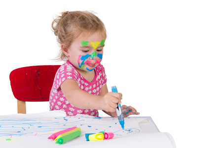 Toddler girl learning how to draw with coloring markers, her face painted with markers, isolated on white photo