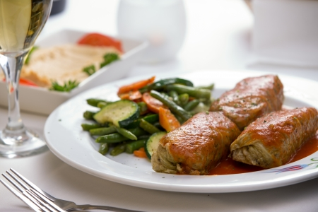 Turkish stuffed cabbage rolls served along with steamed green beans, carrots and zucchini, complemented with hummus plate and white wine.