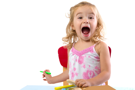 mouth opened: Toddler girl learning at the table very excidted , her eyebrowns are raised and mouth opened large holding colorful markers