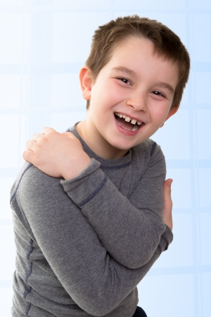 high spirited: Young kid expressing his happiness while his arms closed, body language shows he is hiding something or he just revealed his funny secrets