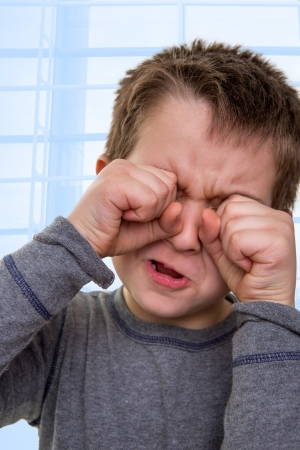 problem: Eight years old kid crying while his hands are on his face touching his eyes, something very sad for him Stock Photo