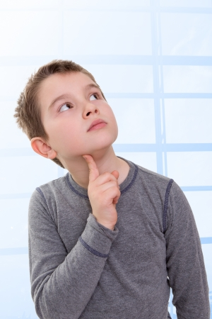 eight years old: Eight Years old Kid looking up thinking, wondering about something, perhaps math problems Stock Photo