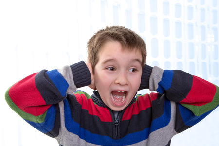 Eight Years old young boy screams with his hands on his ears, perhaps he has some issues