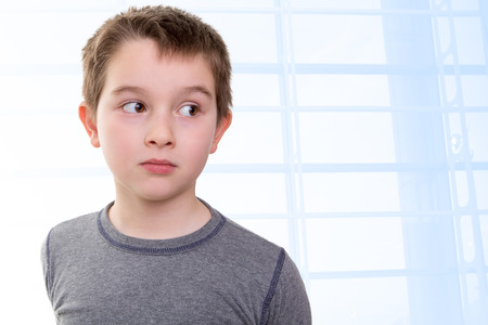 accusing: Eight years old kid looking out skeptically accusing with his big eyes