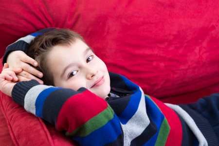 self expression: Young boy on the red couch comfortably relaxing and looking at you with confidence, perhaps he has been counseling by psychiatrist Stock Photo