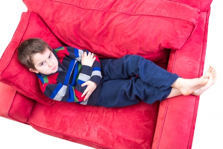 impish: Eight years old boy expression mischievousness with arms closed on the couch by looking up in to your eyes, isolated on white