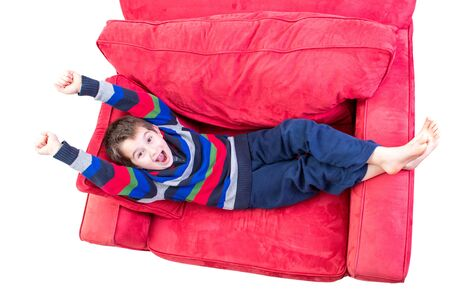 chirpy: Eight years old kid promoting a feeling of cheer on the red couch, isolated on white Stock Photo