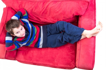 Young boy in his comfort zone, laying down on the red couch comfortably bare foot