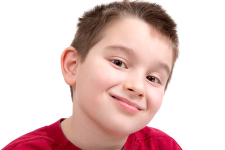 Young boy looking at you appreciatively with a nice smile, isolated on white photo