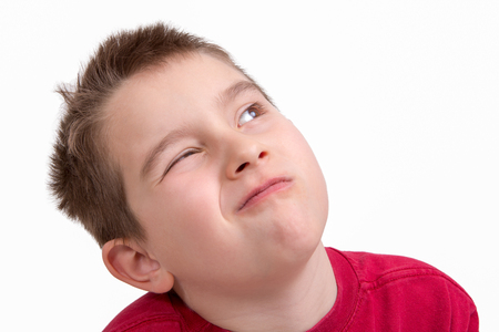 Nine years old kid giving a choosy look with one eye closed
