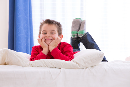 Eight years old kid cheerfully enjoying the morning with Chrismas colors red shirt and green socks photo