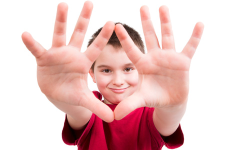 lifted hands: Young boy showing his hands and looking at you between them with confident, all ten fingers are visible