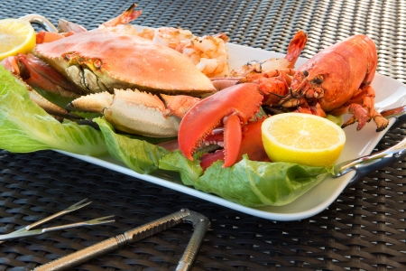 lobster dinner: Red lobster, dungenees crab and jumbo Shrimps on a plate along with sea sheller utensils