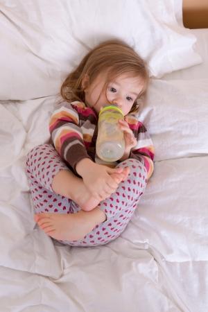 寝る準備をして、眠りに落ちる前に彼女の飲み物を有する幼児の女の子
