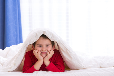 Close up portrait of a eight years old boy laying on the bed looking at  you under his warm blanket. He looks happy and relaxed. photo