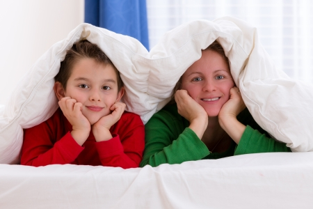 Mother and her son under the blanket with Christmas color pajamas, smiling to you photo