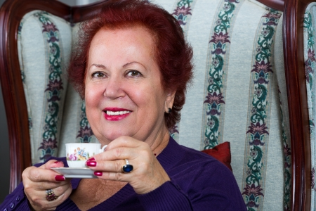 Senior woman having strong Turkish coffee and have a pleasant smile on her face photo
