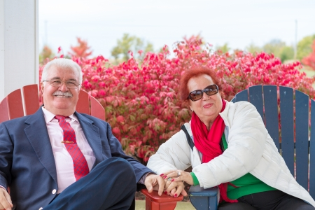 Happy and romantic senior couple smiling at you genuinely, sitting on beach chairs autumn times and burning bushes behind them photo