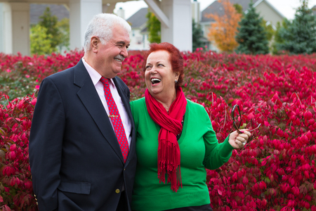 burning bush: Happy and healthy senior enjoying autumn by the burning bush shrubs, she is wearing Christmas colors, red scarf and green shirt he has suit and tie