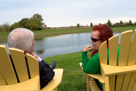 Senior Couple enjoying their togetherness by the pond on the yellow beach chairs photo