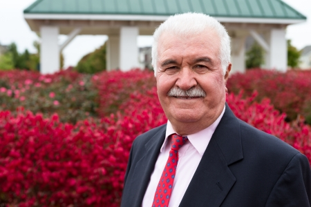 White hair Senior Businessman outside by the red burning bushes photo