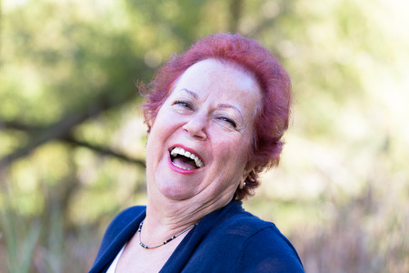 avid: Red hair enthusiastic senior woman giving a genuine laugh