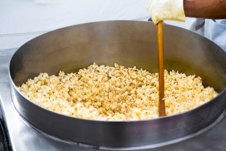 going crazy: Twirling popcorns in the huge pan going crazy and popping