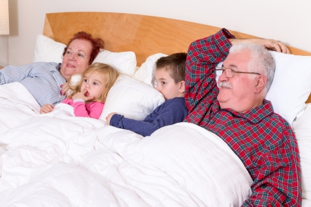 Grandparents watching TV in the bed with their grand kids, they look excited, perhaps its an adventure movie Stock Photo - 23557616