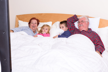 Grandparents watching TV in the bed with their grand kids, they look excited, perhaps its an adventure movie Stock Photo - 23557611