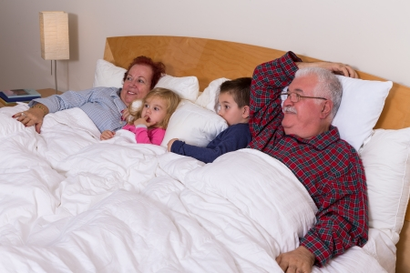 they are watching: Grandparents watching TV in the bed with their grand kids, they look excited, perhaps its an adventure movie Stock Photo