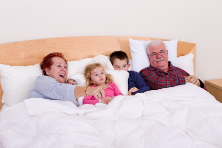 Grandparents watching TV in the bed with their grand kids, they look excited, perhaps its an adventure movie Stock Photo